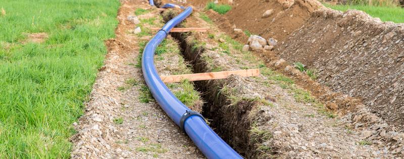 Main water pipe installation across field - Water Main Installation